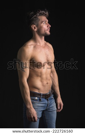 Handsome shirtless muscular man's profile, looking away, isolated on black - stock photo