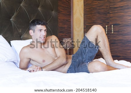 Handsome shirtless young man lying on the bed