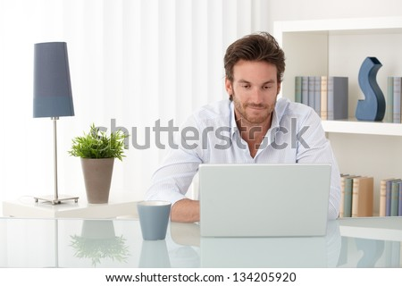 Handsome sitting at living room table, using laptop computer at home, smiling, looking at screen. - stock photo