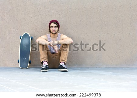 Handsome skateboarder hanging around, sitting against a granite wall, with his skateboard next to him. - stock photo