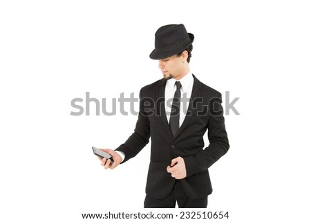 Handsome smart business man in a black and white suit and tie and wearing a trilby hat casually standing looking down to the side at his mobile phone - stock photo