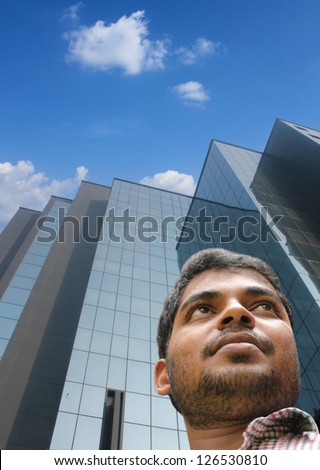 Handsome smart businessman/executive with modern building background looking forward confidently about future. The young adult is of Indian origin
