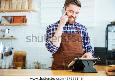 Handsome smiling barista with beard taking order on cell phone and using tablet in cafeteria - stock photo