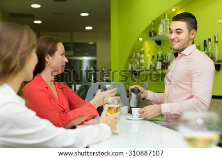 Handsome smiling bartender and two beautiful girls with wine glasses at bar. Focus on man