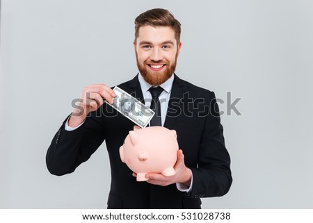 Handsome smiling business man in suit putting money in piggy bank and looking at camera. Isolated gray background