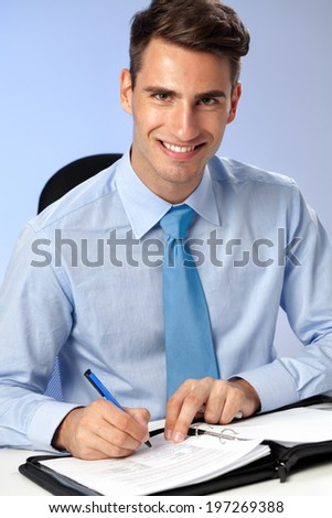 handsome  smiling business writing on papers at office desk - stock photo