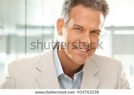 handsome smiling businessman gaze portrait at office - stock photo