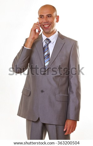 Handsome  smiling businessman in  elegant gray suit  speaking  on the mobile phone  - stock photo