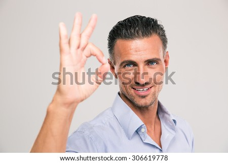 Handsome smiling businessman showing ok sign with fingers over gray background - stock photo