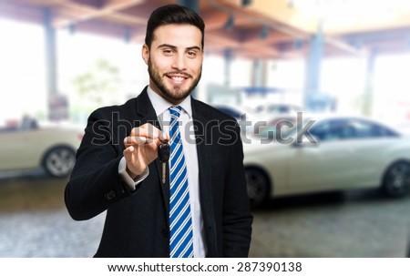 Handsome smiling car dealer lending you the keys - stock photo