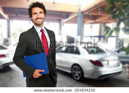 Handsome smiling car dealer portrait - stock photo