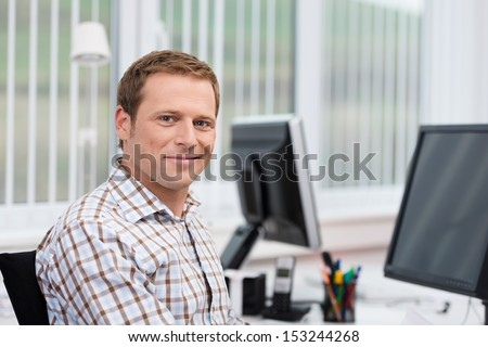 Handsome smiling casual businessman at his desk at the office in front of his computer, head and shoulders looking at the camera - stock photo
