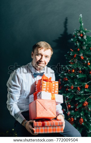 Handsome smiling male with red gift box in hands over christmas tree.