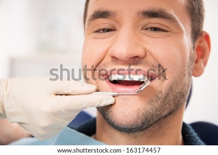Handsome smiling man at doing checkup at dentist's surgery