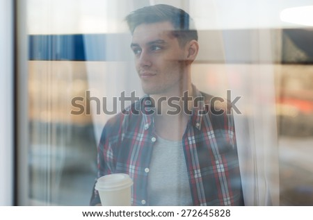 Handsome smiling man guy in plaid shirt looking through the window with a cup of morning coffee concept waiting dreaming. - stock photo