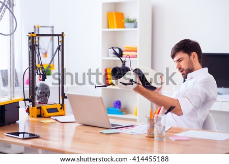Handsome smiling man holding model printed on 3d printer