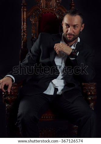 Handsome smiling man in a suit on the throne  - stock photo