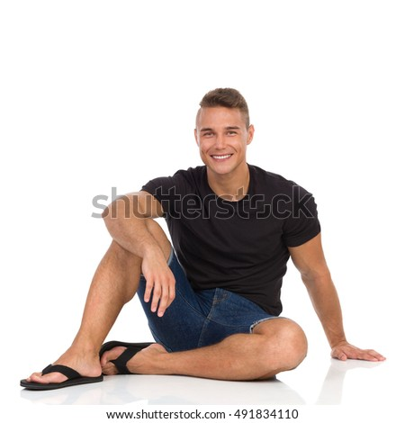 Handsome smiling man in black shirt, jeans shorts and black sandals, sitting on a floor and looking at camera. Full length studio shot isolated on white.