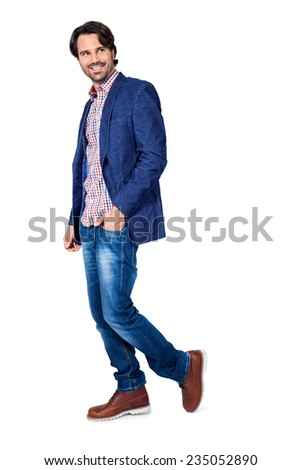 Handsome smiling man in stylish leisurewear approaching the camera in a relaxed posture with his hand in his pocket, isolated on white