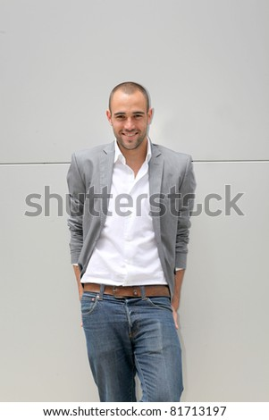 Handsome smiling man leaning on wall - stock photo