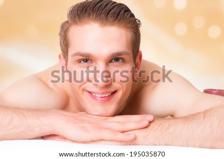 Handsome smiling man lying on the massage desks at the spa salon and relax. Beauty treatment concept.  - stock photo