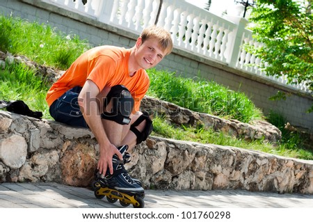 Handsome smiling man  putting on skates going rollerskating in city park - stock photo