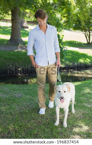 Handsome smiling man walking his labrador in the park on a sunny day - stock photo