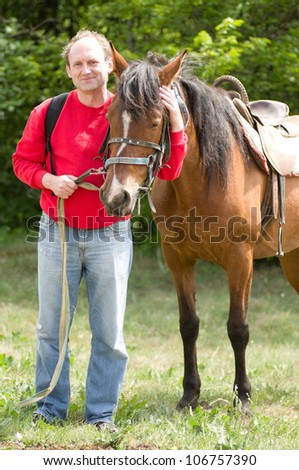 Handsome smiling man with horse in the forest