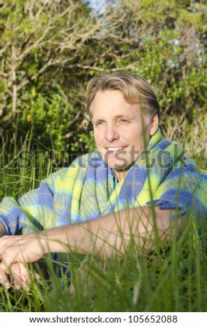 handsome smiling mature blond man sitting in long grass wrapped in a colorful blanket - stock photo