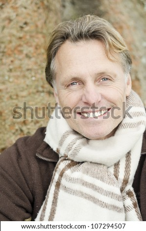 handsome smiling mature blond man wearing a brown pullover and scarf.