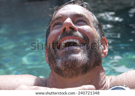 Handsome smiling maturing man in pool / water  - so cute - stock photo