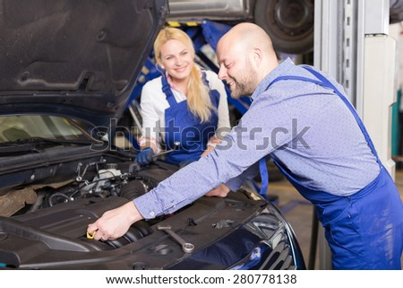 Handsome smiling mechanic and female assistant working at auto repair shop - stock photo