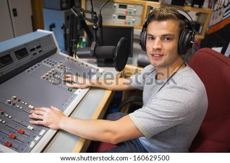Handsome smiling radio host moderating in studio at college - stock photo