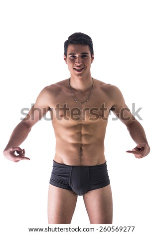 Handsome, smiling, shirtless young man in underwear pointing fingers at empty blank space for copy, isolated on white