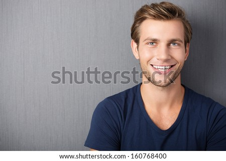 Handsome smiling unshaven young man in a t-shirt standing against a clean blackboard with copyspace , head and shoulders portrait - stock photo
