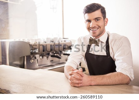 Handsome smiling young barista in his cafe. - stock photo