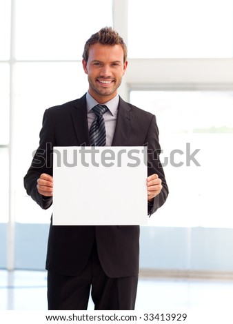 Handsome smiling young businessman showing a white card