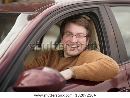 Handsome smiling young man in car - stock photo