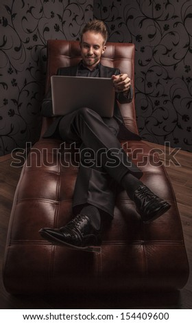 Handsome smiling young man in dark suit with note book relaxing on luxury sofa. - stock photo