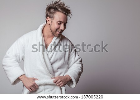 Handsome smiling young man in luxurious bathrobe. - stock photo