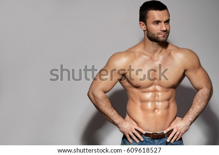 Handsome Smiling Young Man With Sexy Fit Body Posing On Grey Background Indoors. Closeup Portrait Of Healthy Strong Male With Perfect Body Shape And Muscular Abs. Bodybuilding Concept. High Resolution