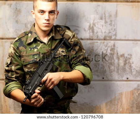 handsome soldier holding gun against an old wall - stock photo