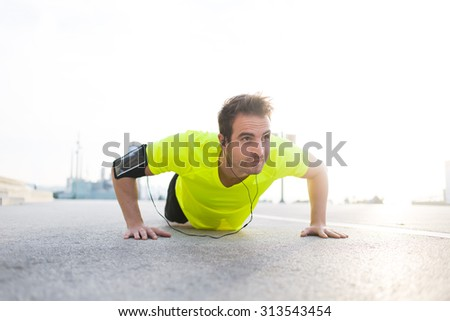 Handsome sports man with running armband doing pushes on asphalt city road while listening to music with headphones,caucasian male jogger warm up before start his workout training outside in morning - stock photo