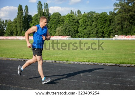 Handsome sportsman is running towards track in stadium. He is looking forward with concentration. There is copy space in right side - stock photo