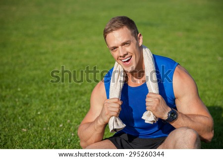 Handsome sportsman is sitting on green grass. He is wiping out his neck with white towel. The man is smiling and looking at camera with joy. There is copy space in left side - stock photo