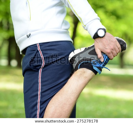 Handsome sportsman stretching outdoors - stock photo