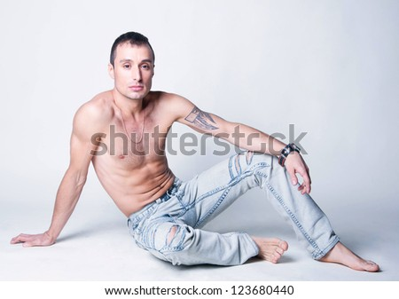 Handsome sporty male model with great body build, tattoo on his left arm, his torso naked, wearing ripped light blue jeans, leather bracelet, sitting on the floor in studio. Light gray background - stock photo