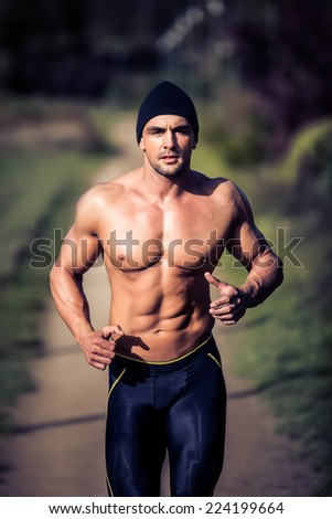 Handsome strong muscular athletic man working out and running outdoors in nature