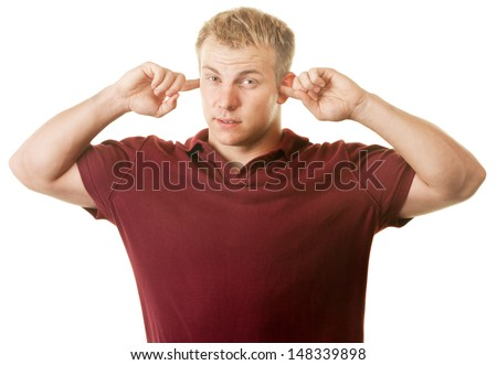 Handsome strong young man with fingers in ears - stock photo