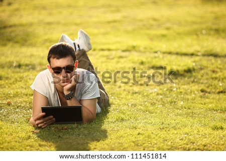 handsome student lying on the lawn with tablet - stock photo
